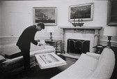 Black & white photograph of JFK in the oval office