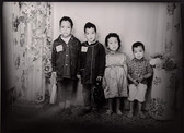 1960s black & white photograph of four children, in a photography studio