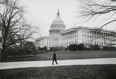 Black & white photograph of JFK walking by the US Capitol building