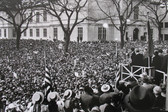 Black & white photograph of JFK speaking to a crowd in a city plaza