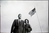 Black & white photograph of JFK, Jackie Kennedy with a US flag