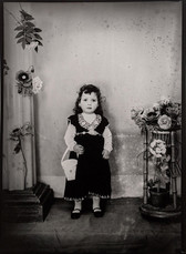 1960s black & white photograph of a young girl wearing an embroidered dress, in a photography studio