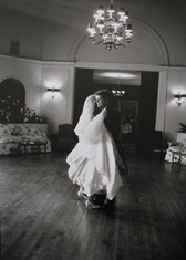 Black & white photograph of a man and woman in bridal dress dancing
