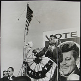 Black & white photograph of JFK during the presidential campaign, speaking to an invisible crowd