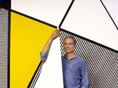"""BOB ADELMAN (1930-2016)  Roy Lichtenstein standing before """"Perfect Painting #1"""" in his studio  photograph 1985 (printed later)  archival pigment print, AP, signed  paper size > 22 x 14 inches"""
