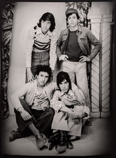1960s black & white photograph of four friends, two standing, two sitting, in a photography studio