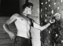 James Dean uses a light meter while shirtless in Roy Schatt's studio in New York City