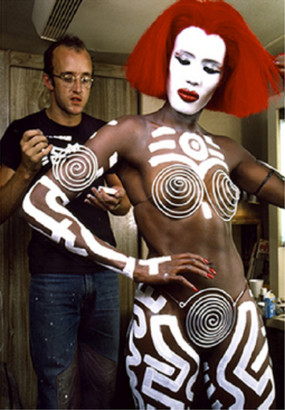 Color photograph of Keith Haring painting white signs the body of performer Grace Jones, wearing in red wig