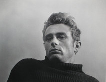 James Dean poses in a torn sweater in New York City while looking downward at the camera