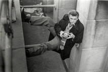 James Dean poses with Rolliflex camera and cigarette while pressed between two walls in New York City alley