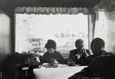 Black & white photograph of Senator Kennedy and Jackie eating at a table in a diner