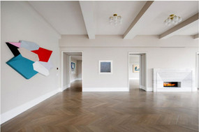 Ballroom with tall ceilings with a colorful shaped painting and an abstract blue print on the walls, and no furniture