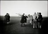 Black & white photograph of Senator Kennedy and staff near an airplane