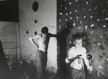 James Dean poses shirtless with another man in the backyard of Roy Schatt's studio in New York City