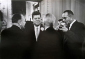 Black & white photograph of JFK speaking to two men