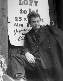 James Dean in a black peacoat posees in from of an ad for a loft for rent in New York City street