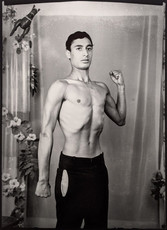 1960s black & white photograph of a young man wearing only trousers, in a photography studio