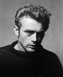 James Dean poses in a torn sweater in New York City while staring forward