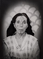 1960s black & white portrait of Amazigh woman with facial tattoos, wearing patterned dress, in a photography studio