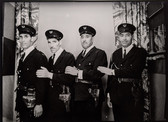 1960s black & white photograph of four policemen in uniform, in a photography studio