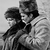 """Photograph by Hatami (1928-2017) Julie Christie and Omar Sharif in a scene where Lara must depart, on the set of """"Doctor Zhivago"""" photograph 1965  vintage gelatin silver print, inscribed 9.5 x 7.5 inches"""