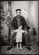 1960s black & white photograph of father and toddler in a photography studio