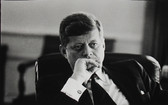 Black & white photograph of JFK in a pensive stance