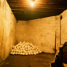 """Nobuho Nagasawa Interior View of Bunker Motel: Emergency Womb, 1995 steel sand, sugar, military bags, army cots, plaster, light, candles  From """"Peace Sculpture 1995,"""" Thyboron, Denmark, 1995"""