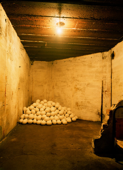 """NOBUHO NAGASAWA Interior View of Bunker Motel: Emergency Womb (1995) steel sand, sugar, military bags, army cots, plaster, light, candles  Installation from """"Peace Sculpture 1995"""" in Thyboron, Denmark, 1995."""