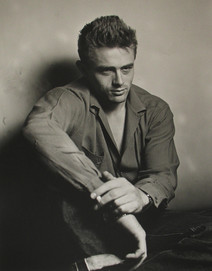 James Dean poses against wall while smoking and staring forward