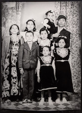 1960s black & white photograph of a family (mother, father, six children) in a photography studio