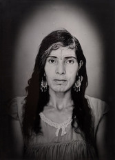 1960s black & white portrait of Amazigh woman with facial tattoos, in a photography studio