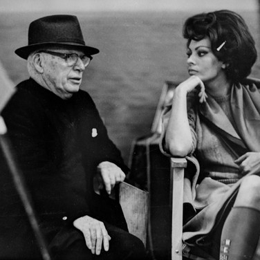 """Photograph by Hatami (1928-2017) Sophia Loren and Charlie Chapling on the set of """"A Countess from Hong Kong,"""" Pinewood Studios, Buckinghamshire photograph 1966 vintage gelatin silver print, signed, stamped 9.5 x 14.5 inches"""