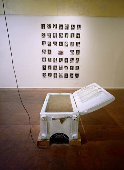 """NOBUHO NAGASAWA Cowboy's Dream (1992) refrigerator, earth, motor, speakers, and 47 photographs dimensions variable  Installation from """"The Atomic Cowboy: The Daze After"""" at Daniel Saxon Gallery, Los Angeles, CA, 1992."""