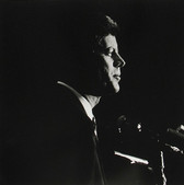 Black & white photograph of JFK in profile, lit from behind