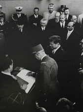 Black & white photograph of JFK with Charles de Gaulle and other officials