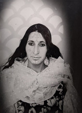 1960s black & white portrait of Amazigh woman with facial tattoos, wearing white scarf, in a photography studio