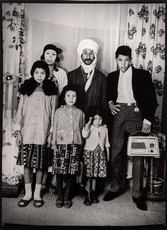 1960s black & white photograph of a family, mother, father and four children, in a photography studio