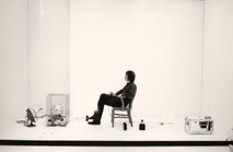 Artist Roger Welch seated in chair during a performance at the Art Institute of Chicago