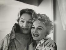 Marlene Dietrich poses with hand around Eva Gabor in New York City, 1950s
