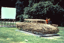 Sculptural video installation outdoors of a Cadillac made of twigs facing drive-in movie footage