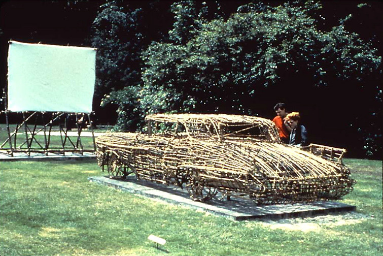 ROGER WELCH Drive-In: Second Feature (1982) Twigs, tree branches (willow, maple, spruce, pine),bamboo, twine and adhesive to bind knots, 16 mm film installation Car size: 60 x 72 x 216 inches | 152.4 x 182.9 x 548.6 cm  Exhibited at the Whitney Museum of American Art, New York, 1982 Collection of the Guggenheim Museum, New York