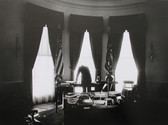 Black & white photograph of a silhouette outlined in the Oval Office, reading newspapers on a table