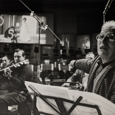 """Photograph by Hatami (1928-2017) Charlie Chaplin conducting the score he composed for """"A Countess from Hong Kong,"""" Pinewood Studios, Buckinghamshire photograph 1966 vintage gelatin silver print, signed, stamped 14.5 x 9.5 inches"""