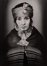 1960s black & white portrait of Amazigh woman with facial tattoos, wearing striped outfit, in a photography studio