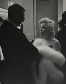 Marilyn Monroe in white fur coat talks with Arthur Miller at a reception, 1956