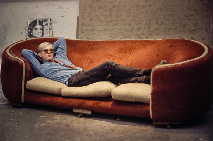 BOB ADELMAN (1930-2016) Andy Warhol on the red Factory couch with a silk-screened 'Jackie' in the background  photograph 1965 [printed later] archival pigment print Paper Size: 13 x 19 inches | 33.0 x 48.3 cm  Also available:  archival pigment print on Kodak paper, edition of 50, stamped by the Bob Adelman estate Paper Size: 16 x 20 inches | 40.6 x 50.8 cm  The red couch was used in several of Warhol's early 1960s films including the 1964 film 'Couch.'
