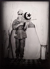 1960s black & white photograph of a soldier in uniform, with a rifle and Islamic flag, in a photography studio