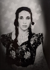 1960s black & white portrait of Amazigh woman with facial tattoos, wearing flowered dress, in a photography studio
