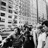 """Photograph by Hatami (1928-2017) Roman Polanski, Mia Farrow, John Cassavetes and crew in front of The Dakota building, New York City, on the set of """"Rosemary's Baby"""" photograph 1968 vintage gelatin silver print, signed, stamped 9.75 x 7.5 inches"""